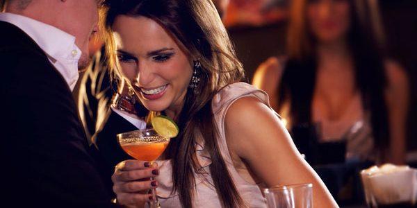 mulher com drink na mao interessada em um homem e rindo