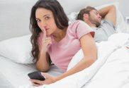 mulher vigiando celular de homem dormindo